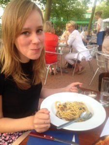 Mijn dochter zit aan een bordje pasta op een terras